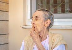 Sehr alte ältere Frau, die ihren Mund mit ihrer Hand schließt lizenzfreie stockfotografie