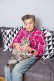 Sehr alte ältere kaukasische Großmutter mit dem grauen Haar und den tiefen Falten sitzt zu Hause auf der Couch in den Jeans und i lizenzfreies stockbild