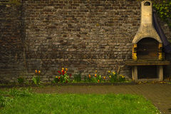 Sehr alte Backsteinmauer mit eingebautem Grill, helle Tulpen auf dem Hintergrund des alten Ziegelsteines Lizenzfreies Stockfoto
