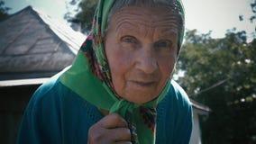 Sehr alte Frau allein in einem Schal am Garten im Freien stock video footage