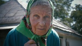 Sehr alte Frau allein in einem Schal am Garten im Freien stock footage