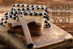 Sehr alte heilige Bibel und hölzernes Kreuz Stockbilder