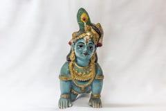Sehr alte kleine Lord krishna Puppe mit den traditionellen oranments gemalt in der blauen Farbe gelegt in einen weißen Hintergrun Stockfotografie