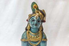 Sehr alte kleine Lord krishna Puppe mit den traditionellen Verzierungen gemalt in der blauen Farbe gelegt in einen weißen Hinterg Stockfotografie