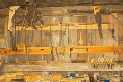 Sehr alte rostige Holzbearbeitungswerkzeuge auf der Wand in der Werkstatt Lizenzfreie Stockbilder