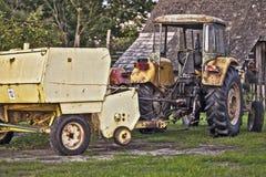 Sehr alte Strohpresse und gelber Traktor Stockfotografie