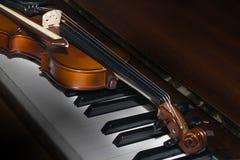 Sehr alte Violine, die auf dem Klavier liegt stockbilder