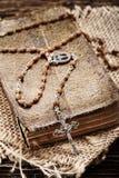 Sehr altes Gebetsbuch und Weinleserosenbeet auf hölzernem Hintergrund Lizenzfreies Stockfoto