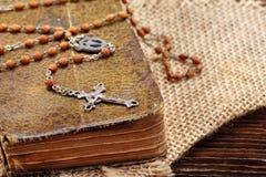 Sehr altes Gebetsbuch und Weinleserosenbeet auf hölzernem Hintergrund Stockfotos
