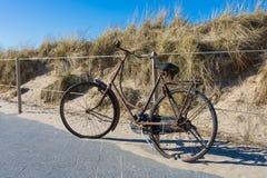 Sehr altes und rostiges Fahrrad, verschlossen zu einem modernen Stahlzaun stockfoto
