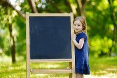Sehr aufgeregtes kleines Schulmädchen durch eine Tafel Stockbilder