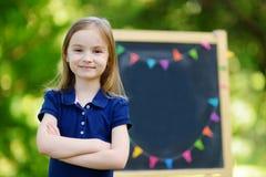 Sehr aufgeregtes kleines Schulmädchen durch eine Tafel Lizenzfreies Stockfoto