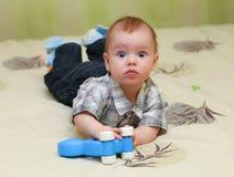 Sehr überraschtes Baby, das auf dem Bett liegt Stockfotografie
