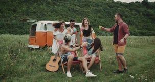 Sehr charismatische Freunde am Picknick, irgendein Getränk und Beifall mit einander mitten in Feld trinkend stock footage