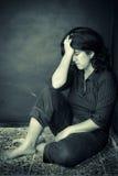 Sehr deprimierte Frau, die auf einer Ecke sitzt Stockbild