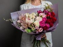 Sehr empfindlicher handgemachter Blumenstrauß in den Händen des Mädchenfloristen, der großen Geschenk-, neuen und ordentlichen, i lizenzfreie stockfotografie