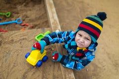Sehr ernstes Kind, das mit Spielwaren im Sandkasten spielt stockfotografie