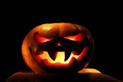 Sehr furchtsamer Halloween-Kürbis lokalisiert auf schwarzem Hintergrund mit i Lizenzfreie Stockfotos