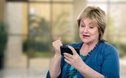 Sehr gestörte ältere Frau hat beweglichen Videochat Lizenzfreie Stockfotos