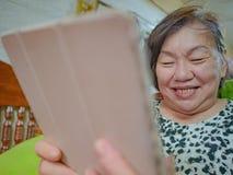 Sehr glückliche alte asiatische Frauen betrachten die Tablette in ihrem Haus lizenzfreie stockbilder
