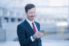 Sehr glücklicher Geschäftsmann, der sein Mobiltelefon betrachtet Stockfotos