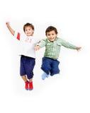 Sehr glückliches Springen mit zwei wenig nettes Kindern Lizenzfreie Stockfotos