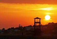 Sehr große glühende goldene Sonne stellt hinter einen hölzernen Ausblickkontrollturm auf einem schönen sandigen Strand in Spanien  Stockbild