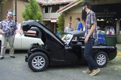 Sehr großer Mann und ein sehr kleines Auto Stockbild