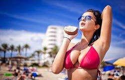 Sehr heiße Holdingkokosnuß der jungen Frau am Strand Lizenzfreie Stockfotografie