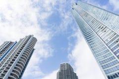 Sehr hohe Wolkenkratzer mit den Wolken, die vorbei treiben stockbilder