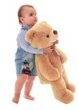 Sehr kleiner Junge trägt einen Teddybären Lizenzfreie Stockbilder