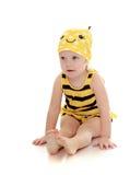 Sehr kleines Mädchen in einem gestreiften Bienenkostümsitzen Lizenzfreie Stockfotografie