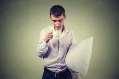 Sehr müde, den Geschäftsmann einschlafend, der einen Tasse Kaffee und ein Kissen hält Lizenzfreie Stockfotografie