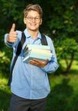 Sehr nett, Junge in den runden Gläsern und blaues Hemd mit Rucksack hält Bücher im Park Bildung, zurück zu Schule lizenzfreies stockbild