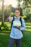 Sehr nett, Junge in den runden Gläsern und blaues Hemd mit Rucksack hält Bücher im Park Bildung, zurück zu Schule lizenzfreie stockfotografie