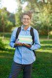 Sehr nett, Junge in den runden Gläsern und blaues Hemd mit Rucksack hält Bücher im Park Bildung, zurück zu Schule stockbild