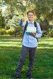 Sehr nett, Junge in den runden Gläsern und blaues Hemd mit Rucksack hält Bücher im Park Bildung, zurück zu Schule stockbilder
