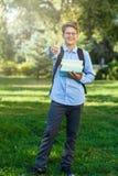 Sehr nett, Junge in den runden Gläsern und blaues Hemd mit Rucksack hält Bücher im Park Bildung, zurück zu Schule stockfotos