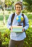 Sehr nett, Junge in den runden Gläsern und in den headphhones und blaues Hemd mit Rucksack hält Bücher, Kugel im Park Ausbildung lizenzfreies stockfoto