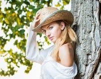 Sehr nette blonde Frau, die sich im Freien mit einem Hut nahe einem Baum hinsetzt Stockfoto