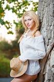Sehr nette blonde Frau, die sich im Freien mit einem Hut nahe einem Baum hinsetzt Stockbilder