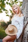 Sehr nette blonde Frau, die sich im Freien mit einem Hut nahe einem Baum hinsetzt Stockfotografie