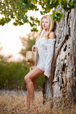 Sehr nette blonde Frau, die sich im Freien mit einem Hut nahe einem Baum hinsetzt Stockfotos
