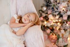 Sehr nette Blondine des kleinen Mädchens im weißen Kleid, das auf einem Stuhl a sitzt stockbild