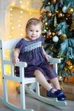 Sehr nette reizend Blondine des kleinen Mädchens im lila Kleid, das laut auf einem Kind-` s Schemel und Lachen auf dem Hintergrun lizenzfreies stockfoto