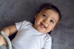 Sehr nettes Baby in der weißen Kleidung, die auf dem Bett liegt Stockfoto