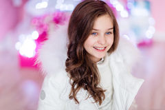 Sehr nettes langhaariges junges Mädchen, das in einer weißen Jacke und in einem s lächelt lizenzfreie stockfotografie