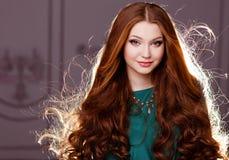 Sehr nettes sinnliches Mädchen mit dem roten Haar hintergrundbeleuchtet Lizenzfreies Stockbild