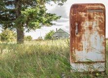 Sehr rostiger antiker alter Kühlschrank, der draußen im Sommer sitzt stockfotografie