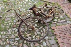 Sehr rostiges Fahrrad, das auf Kopfsteinen liegt Lizenzfreie Stockfotos